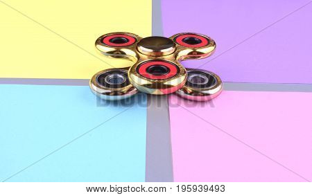 Group of hand fidget spinner toy on colorful and trendy background. Stress and anxiety relief.