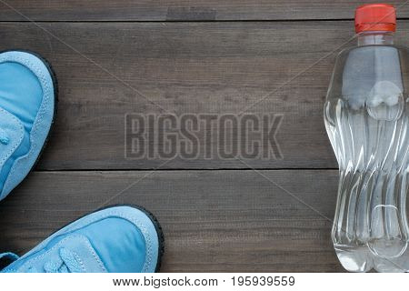 Blue Sneakers And Water Bottle On Dark Background