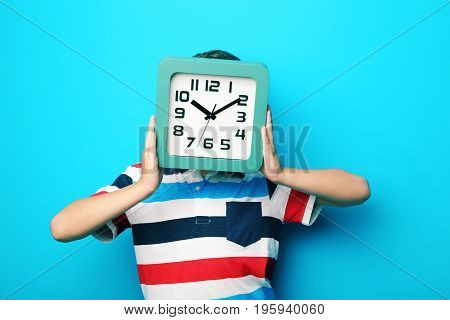 Young Boy With Clock On Blue Background
