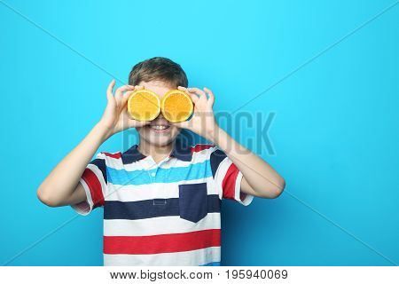 Young boy with orange fruit on blue background