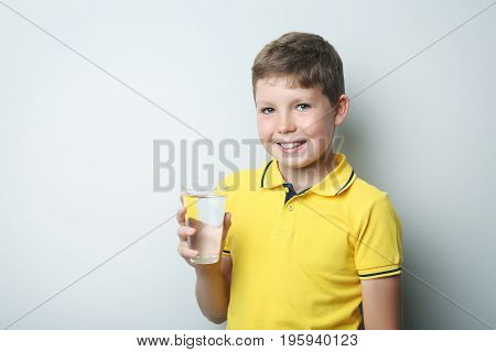 Portrait Of Young Boy With Glass Of Water On Grey Background