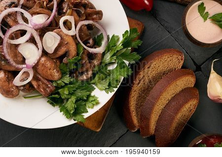 Cooked fried mushrooms on white plate over dark stone background with rye diet bread low-calorie sauce fresh red bell pepper and fragrant garlic top view. Healthy vegetarian food and detox concept