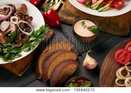 Set of three bowls with different dishes: fried mushrooms fresh low-calories salad with vegetables and grilled chicken breast. Fresh dietary rye bread and branded sauce on dark stone background