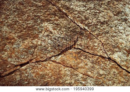 abstract background or texture fissured ocher colored stone