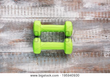 Green dumbbells on the grey wooden table