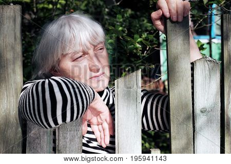 Woman with short gray hair posing with a distant gaze behind the rustic fence. Outdoor portrait