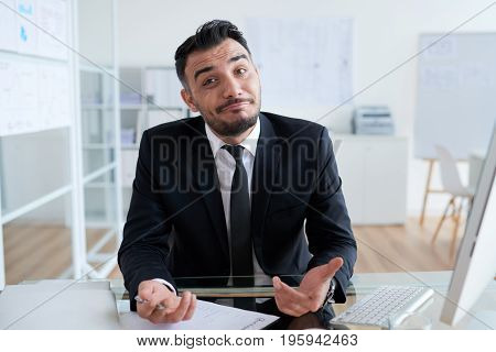 Portrait of confused smiling business executive looking at camera