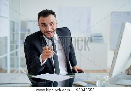 Cheerful entrepreneur smiling and pointing at you with index finder