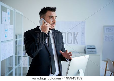 Emotional entrepreneur explaining something to business partner on the phone