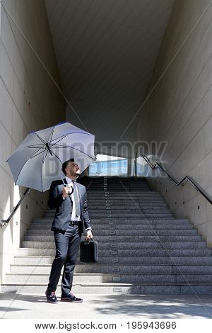 Pensive businessman with umbrella looking at sunny sky: changes for the better