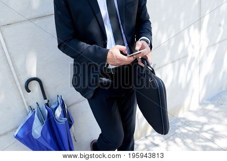Cropped image of businessman leaning on the wall and texting