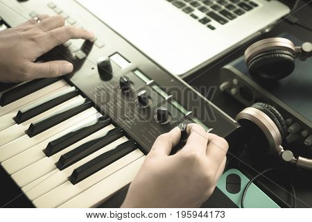 Music keyboard player is adjusting sound on synthesizer