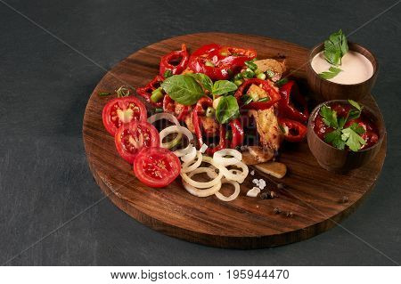 Braised chicken breast with baked vegetables and сhili sauce in a bowl on round wooden board over dark stone background. close-up. horizontal. Healthy low-calories food.