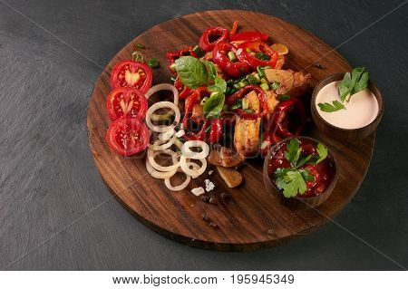 Close-up of grilled spicy chicken breast with fresh baked vegetables and branded garlic sauce on a black stone background. Healthy low-calories food.