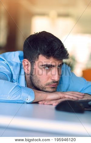 Portrait of a depressed office worker laying on his desk and thinking.