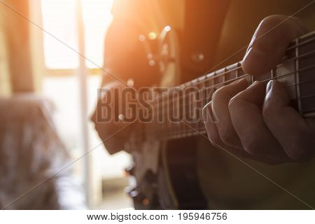The man is playing the guitar in his house