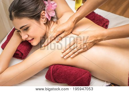 Spa Therapist is rubbing women back with Aroma oil.