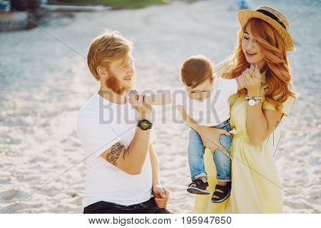 Beautiful red-haired woman with her husband and a wonderful son sitting on a summer beach on the sand