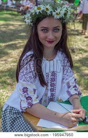 TIMISOARA ROMANIA - JUNE 24 2017: Young girl dressed in traditional Romanian blouse called IE with flower head crown. A show organized by the City Hall on the occasion of the IEI national day.