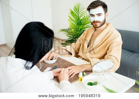 A spa worker does a manicure for a handsome man