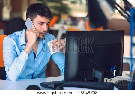 Young businessman busy working on laptop computer while talking on the smart-phone at office.young hipster using laptop sitting at wooden table of modern loft space and looking out the window.flare