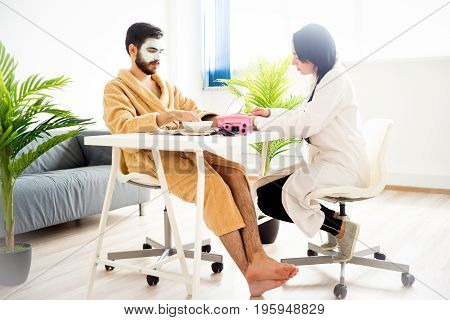 Man is having his nails done at a spa center