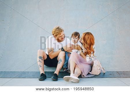 Beautiful red-haired woman with her husband and a wonderful son on a summer city