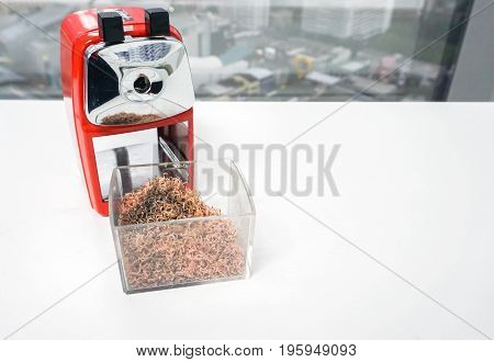 close up pencil sharpener with shavings debris in a trash bin