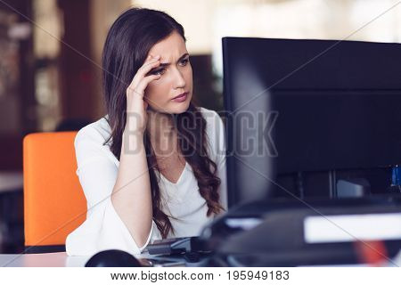 Concentrated middle aged woman working on her computer. Start-up office background.