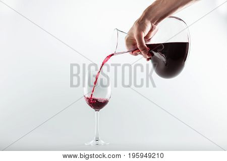 Cropped Shot Of Person Holding Decanter And Pouring Red Wine Into Glass Isolated On White