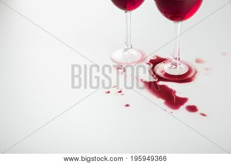 Close-up View Of Wineglasses With Red Wine And Wine Spilled Isolated On White