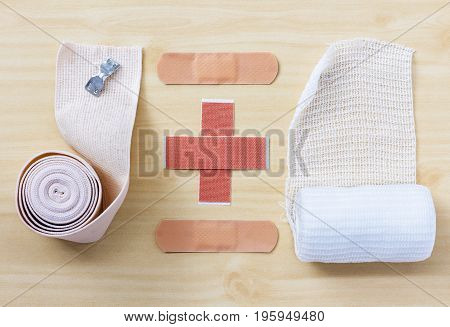 Medical elastic bandage and medical gauze bandage on wood table.