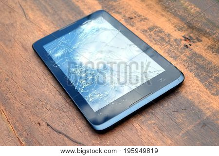 Electronic tablet in black case with broken touch screen on brown wooden background side view closeup