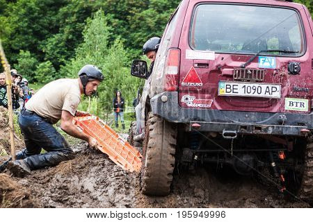 LUBOTIN UKRAINE - JULY 23 2016: RFC Ukraine Wild Boar Challenge 2016. Team using recovery sand tracks to overcome a hard pit.