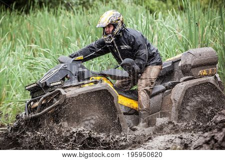 LUBOTIN UKRAINE - JULY 23 2016: RFC Ukraine Wild Boar Challenge 2016. The participant on quad bike passes a deep water pit.