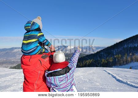 Father, mother and children are having fun and playing on snowy winter walk in nature. The child sits on the shoulders of his father. Frost winter season.