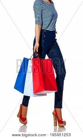 Shopping. The French way. Closeup on modern fashion-monger with shopping bags of the colours of the French flag isolated on white walking