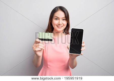 Charming Asian Woman Hand Holding Smartphone And Show Credit Card. Presenting Your Product.