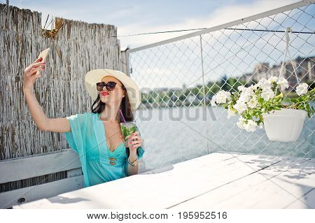 Sweet Young Lady Wearing Hat And Sunglasses With A Cocktail Using Her Smartphone While Sitting By Th