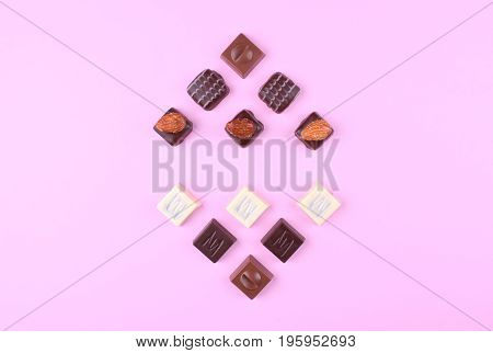 Collection of delicious chocolate pralines on trendy pink background. Flat lay style. Place for your text.