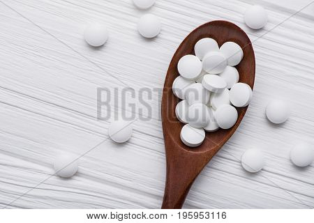 White Medical Pills On Wooden Spoon