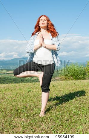 Young Red Haired Woman Is Practicing Yoga