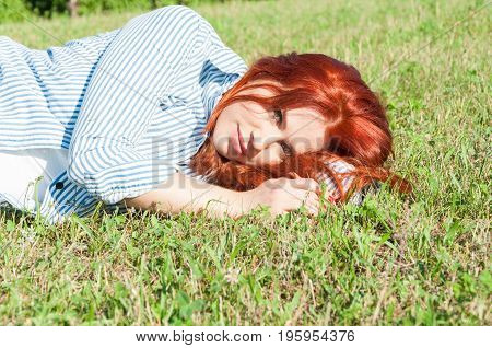 Beautiful Red Haired Woman Lying On Grass Outdoos
