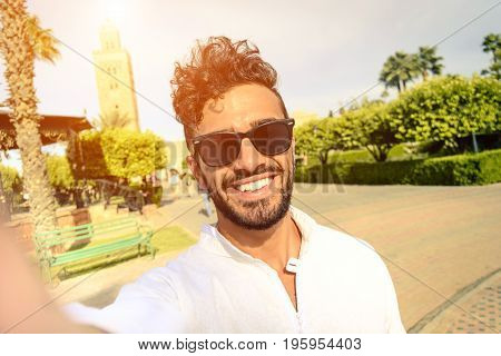Happy young guy take selfie during holiday life moment. Hipster traveler wanderers enjoying exclusive alternative destination make souvenir photo during vacation in Marrakech.