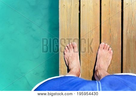 Naked feet on the wooden pier built on the blue water lake. Bare feet nature Background during a summer holiday. Relax concept luxury vacation leisure society. Enjoying good time and magic moments