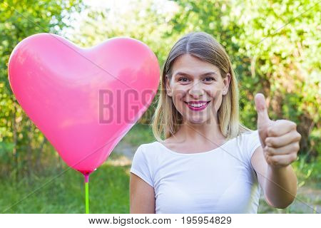 Picture of a smiling beautiful woman holding a red helium balloon ans showing thumbs up outdoor