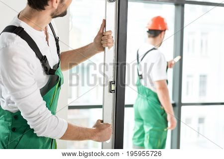 male constructor setting door according to level in modern room. His colleague painting on background
