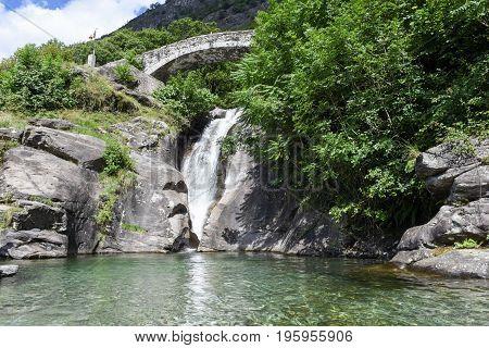 Santa Petronilla Waterfalls With Roman Bridge In Biasca