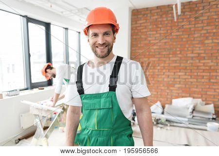 Portrait of master-builder expressing cheerfulness during repair. He looking at camera