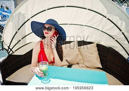 Portrait Of A Stunning Girl In Red Bikini Swimsuit And Sunglasses Talking On Her Phone While Sitting
